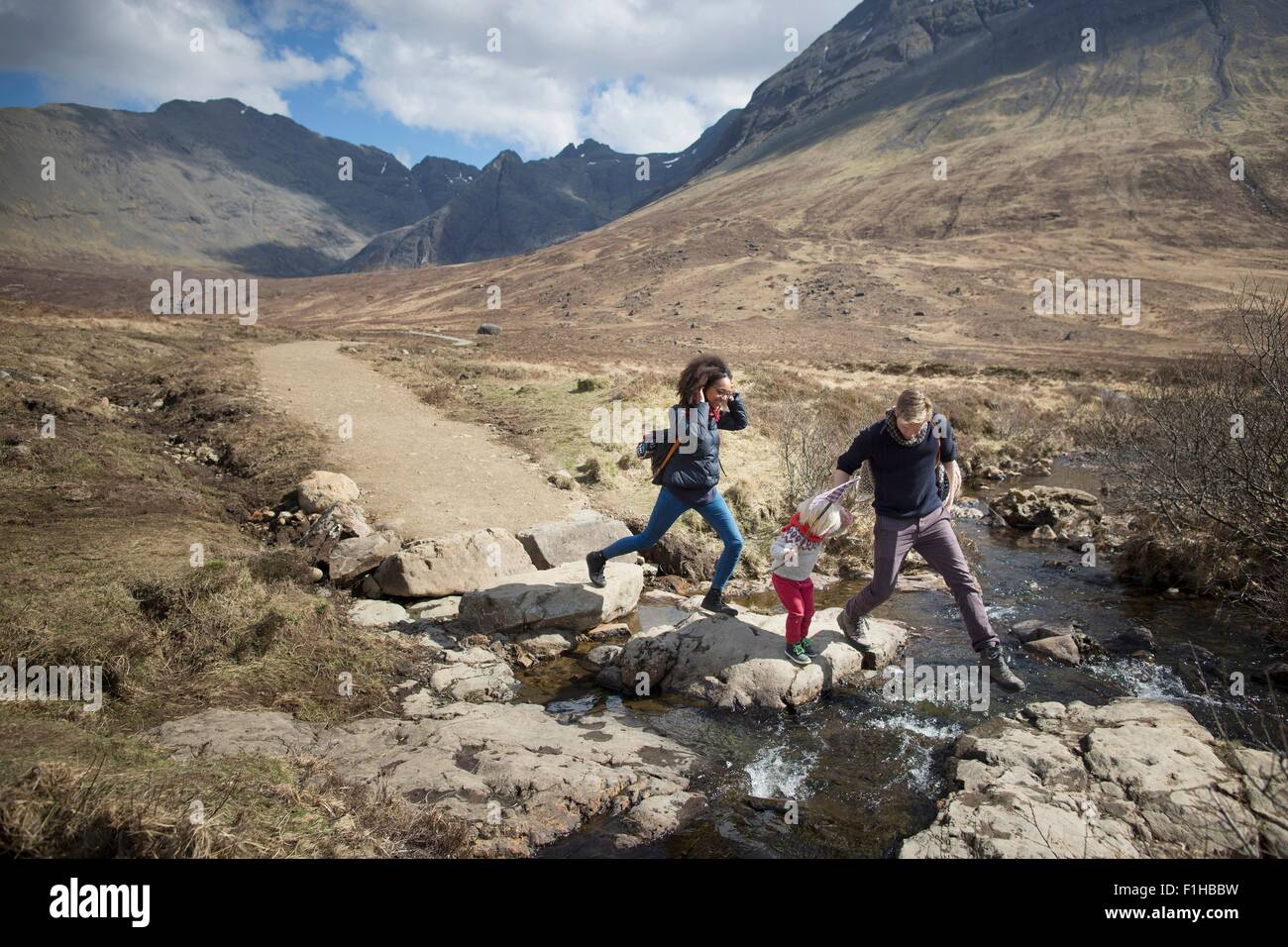 Family crossing stream, Fairy Pools, Isle of Skye, Hebrides, Scotland - Stock Image