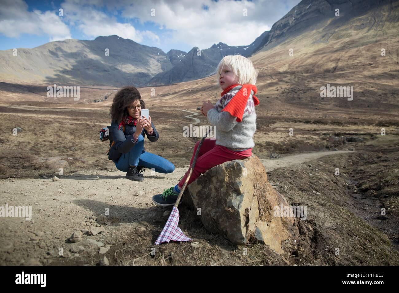 Mother taking photo of son, Fairy Pools, Isle of Skye, Hebrides, Scotland - Stock Image