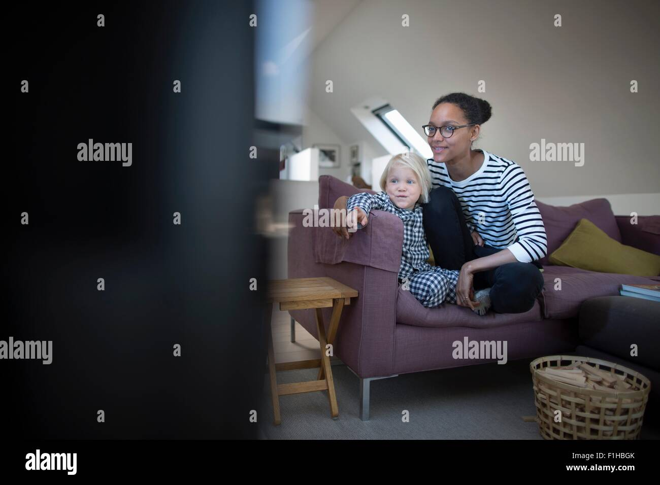 Mother and son sitting on sofa watching television - Stock Image