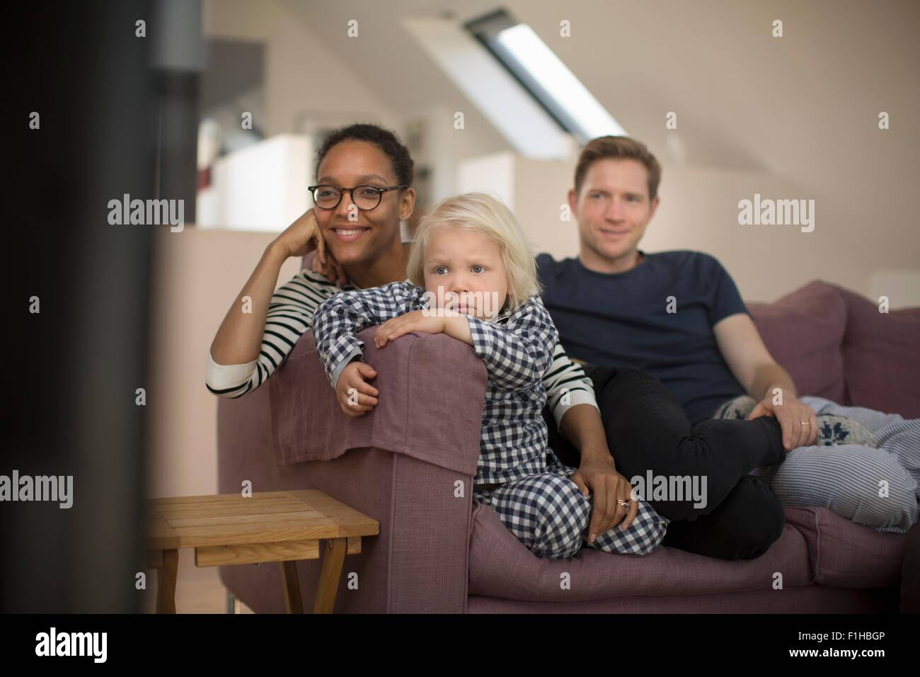 Family sitting on sofa watching television - Stock Image