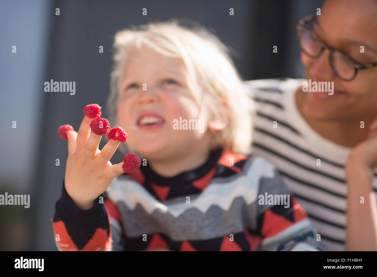 Boy with raspberries on fingers, mother watching - Stock Image
