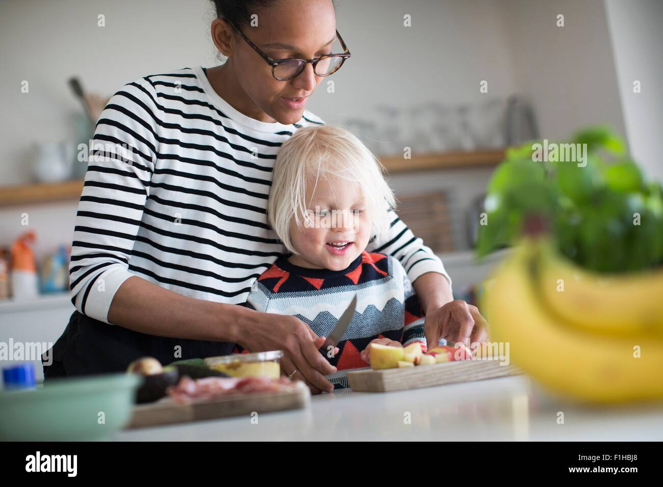 Mother helping sone prepare food in kitchen - Stock Image