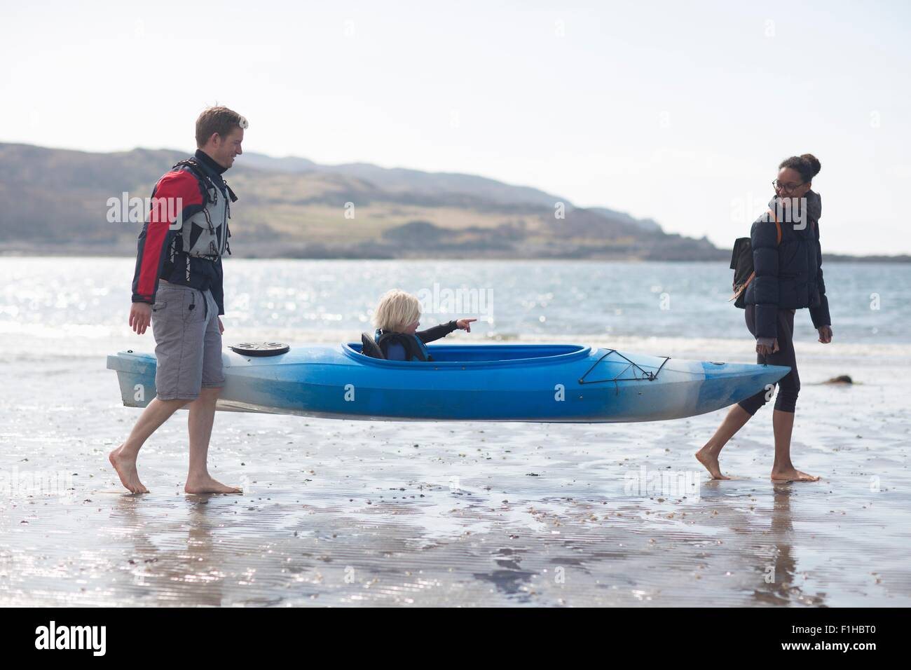 Parents carrying son in canoe on beach, Loch Eishort, Isle of Skye, Hebrides, Scotland - Stock Image