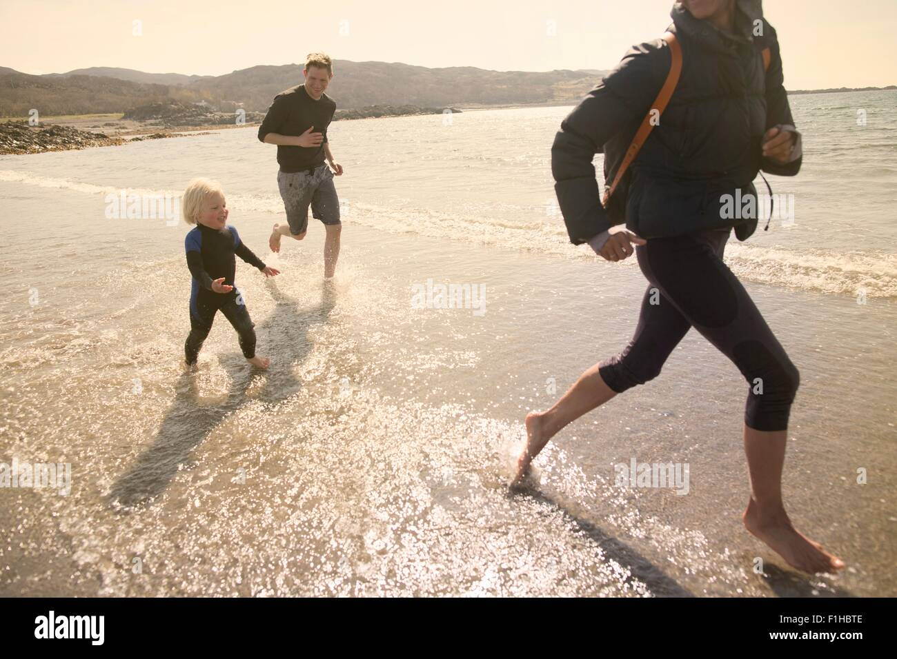 Family running on beach, Loch Eishort, Isle of Skye, Hebrides, Scotland - Stock Image