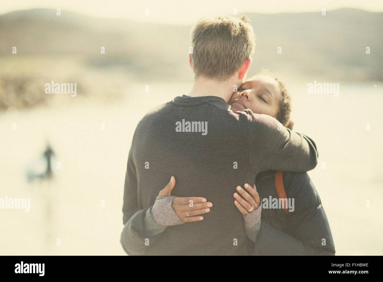 Mid adult couple hugging in sunlight - Stock Image
