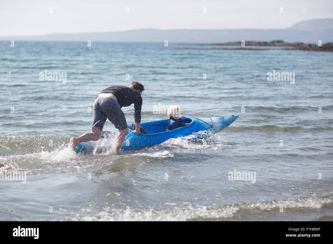 Father pushing son in water in canoe - Stock Image