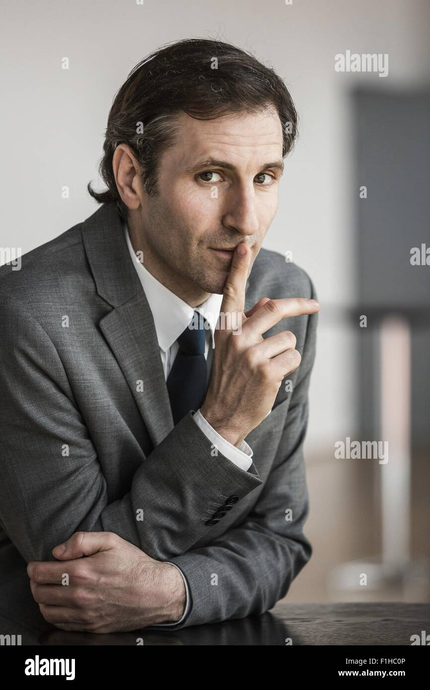 Portrait of mature businessman, finger to lips - Stock Image
