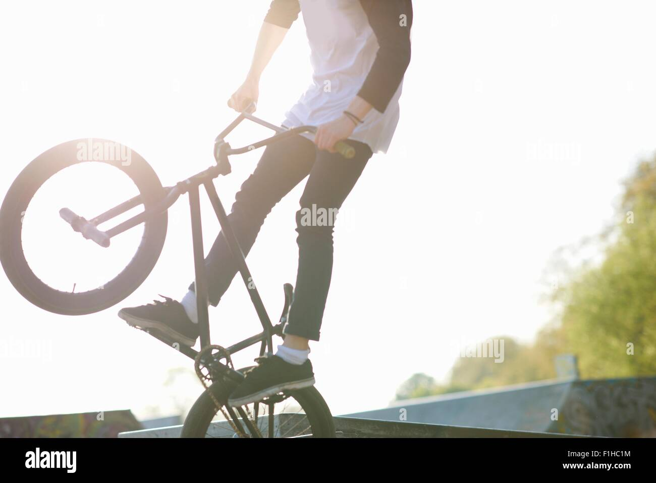 Young man doing stunt on bmx at skatepark - Stock Image