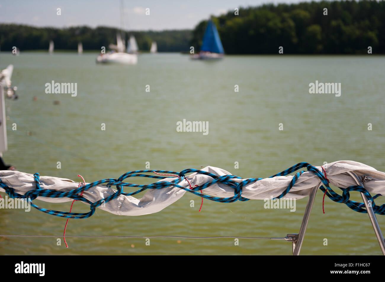 Rolled up mast sail material at Masuria - Stock Image
