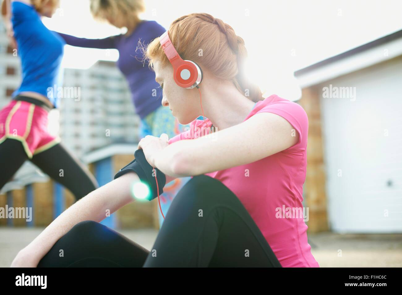 Portrait of woman sitting on floor attaching armband before exercise - Stock Image