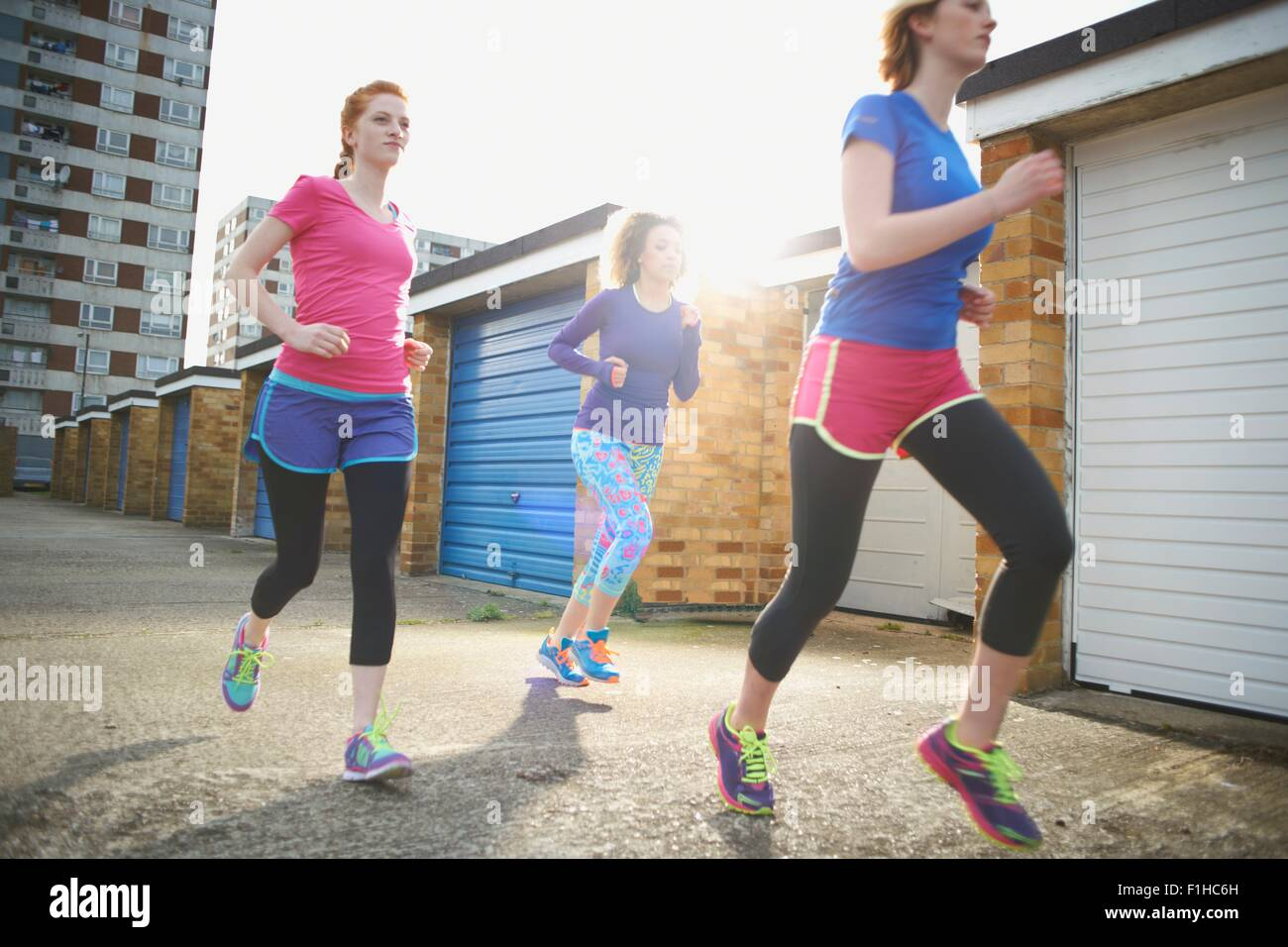 Three women exercising and jogging together - Stock Image