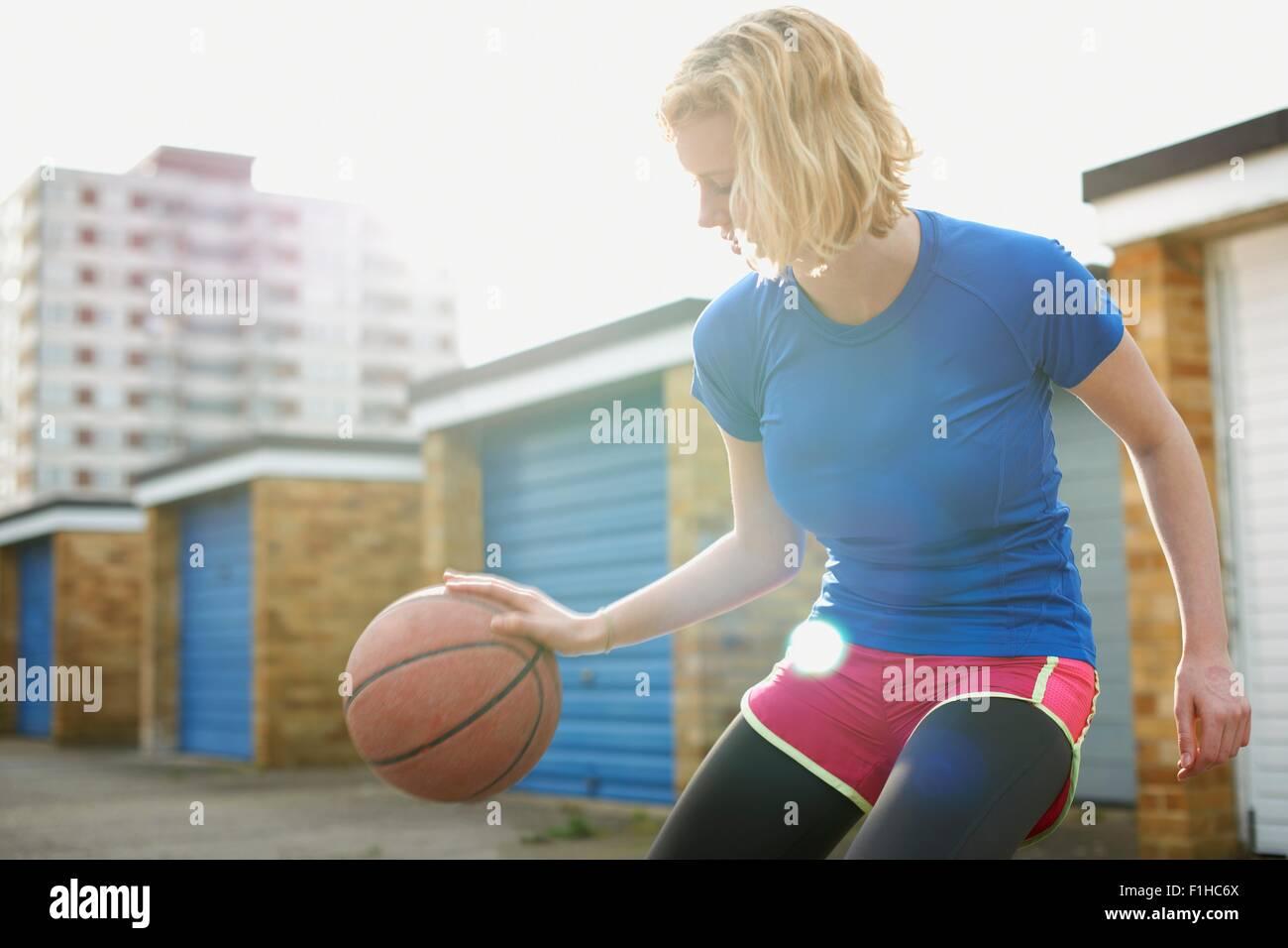 Portrait of woman bouncing basketball - Stock Image