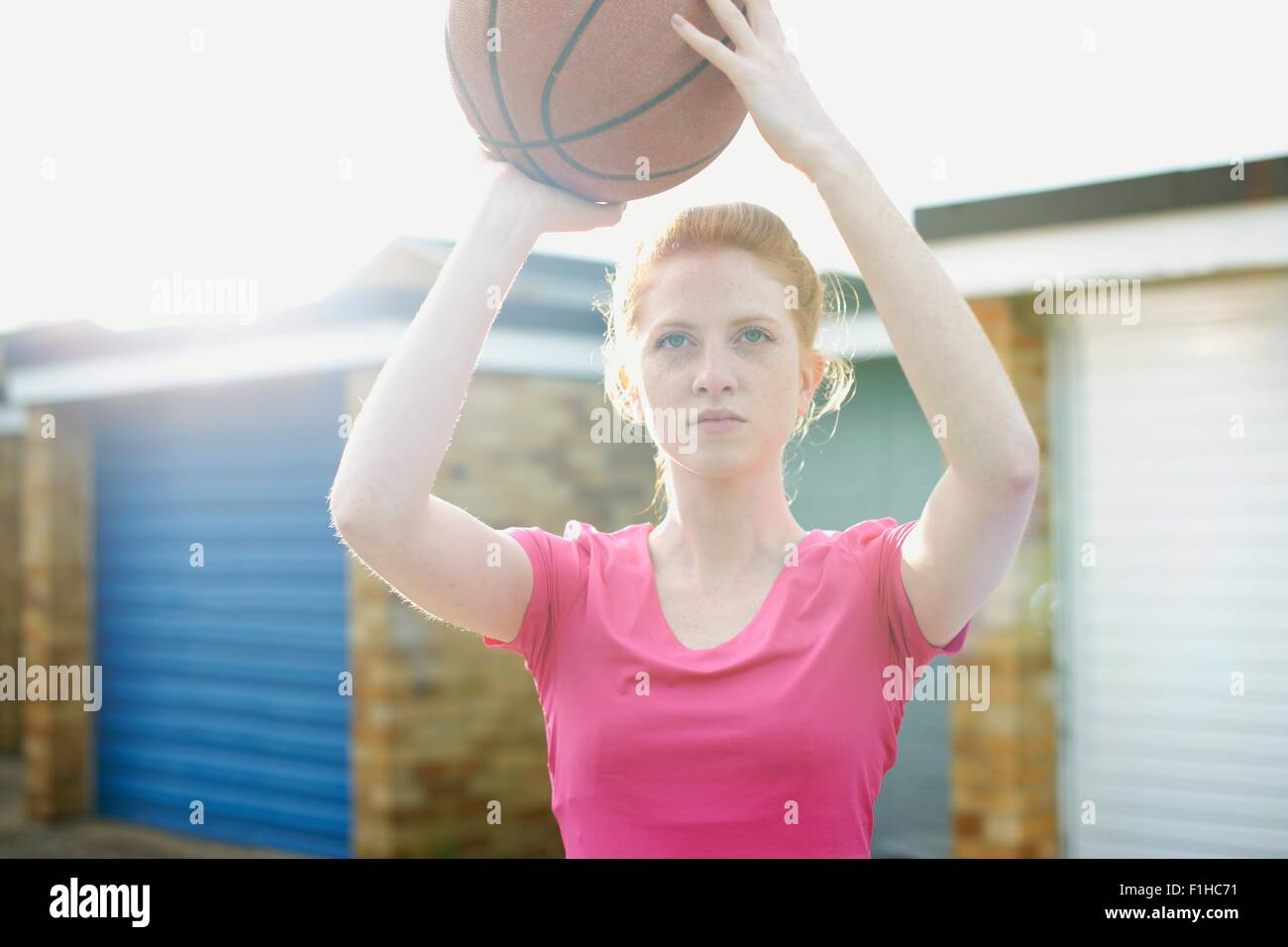 Portrait of woman holding basketball above head - Stock Image