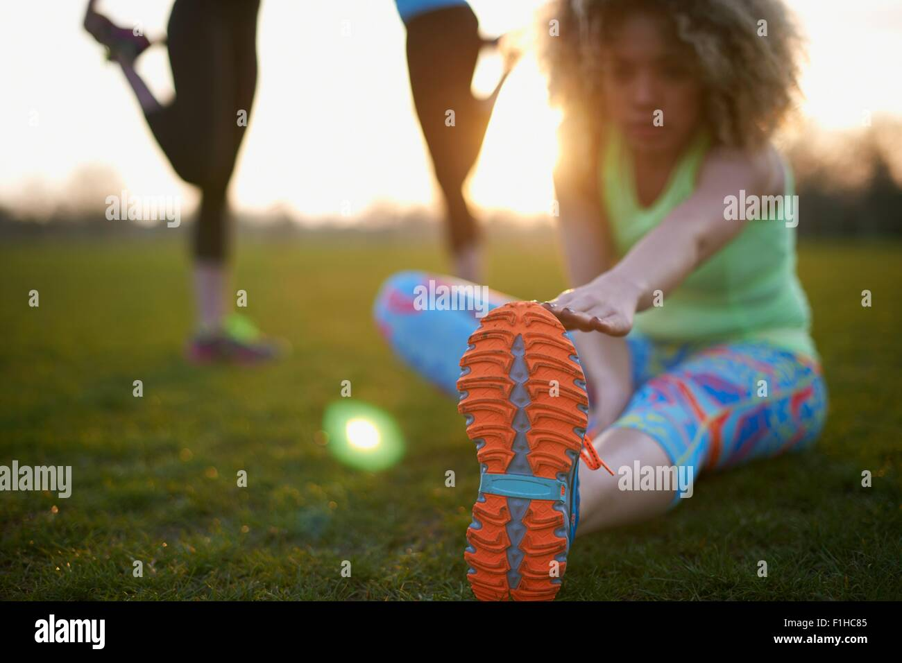 Portrait of woman stretching before exercise in park - Stock Image