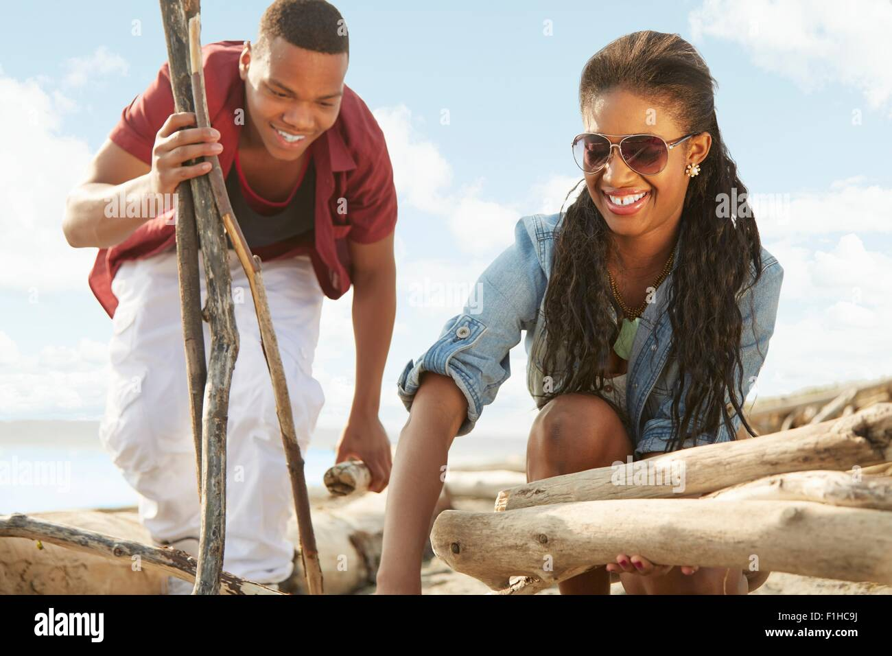 Young couple on beach gathering driftwood together - Stock Image