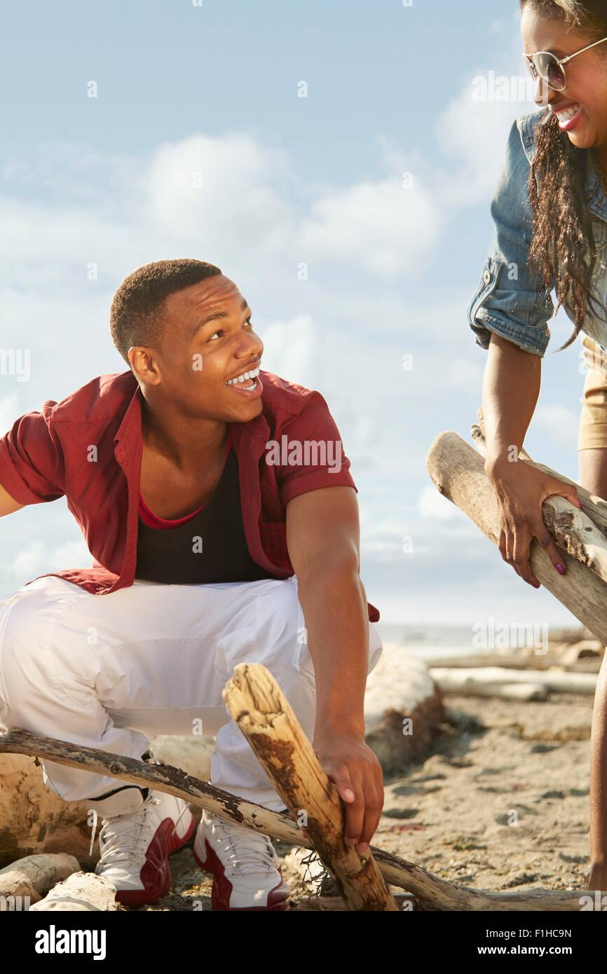 Young couple on beach gathering driftwood together, face to face - Stock Image