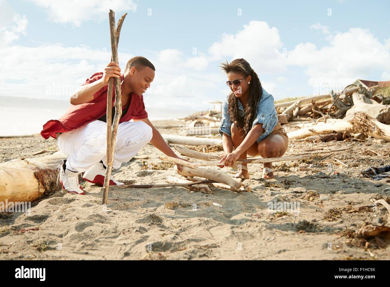 Young couple crouching on beach building campfire with drftwood - Stock Image