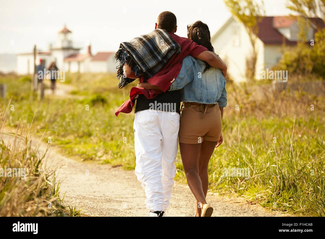Rear view of young couple strolling with arms around each other Stock Photo