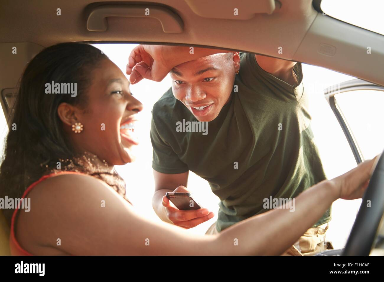 Young man standing at open car door smiling at young woman - Stock Image