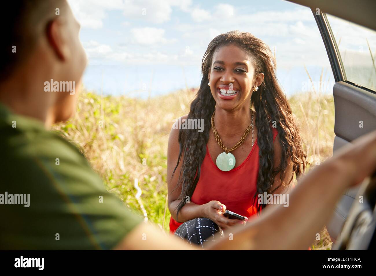 Young woman at open car door holding smartphone smiling - Stock Image