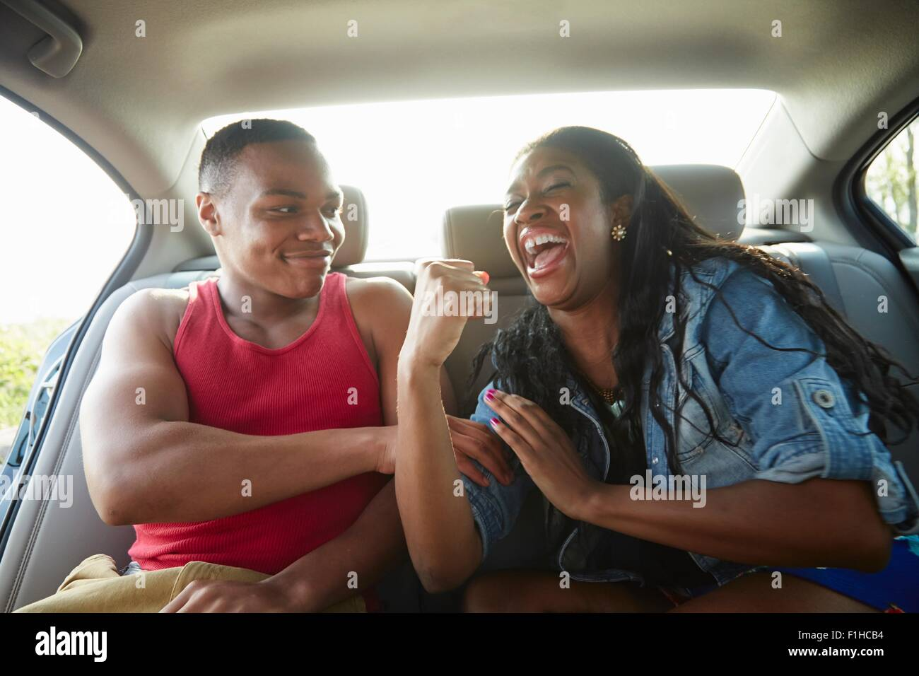 Young couple in car laughing, woman flexing muscles - Stock Image