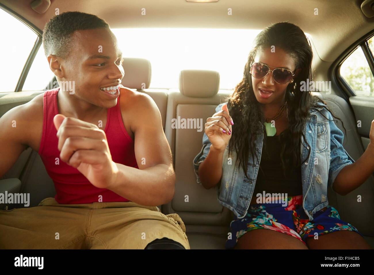 Young couple in back seat of car showing off dance moves - Stock Image