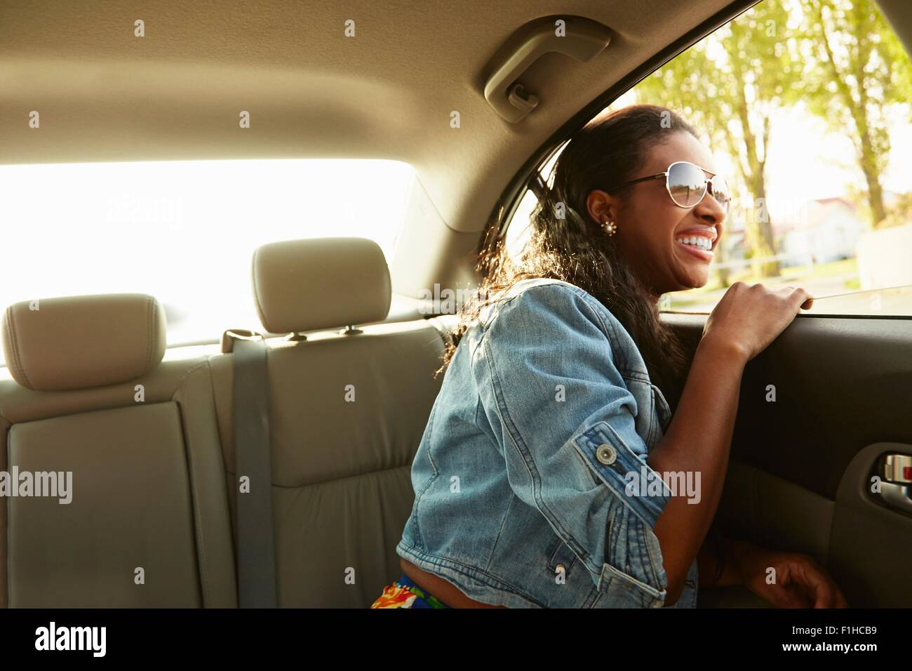Young woman wearing sunglasses looking out of car window - Stock Image