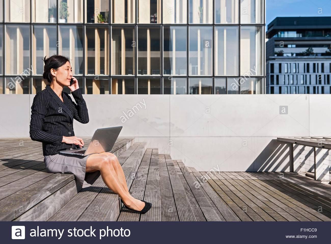 Businesswoman using laptop in front of high rise building, Paris, Île-de-France, France - Stock Image