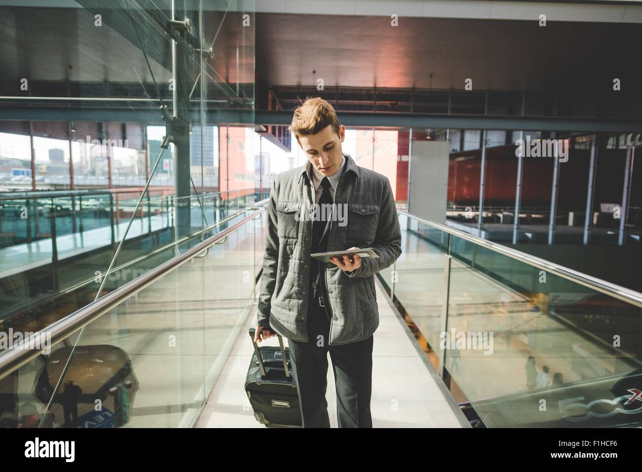 Portrait of young businessman commuter using digital tablet at train station. - Stock Image