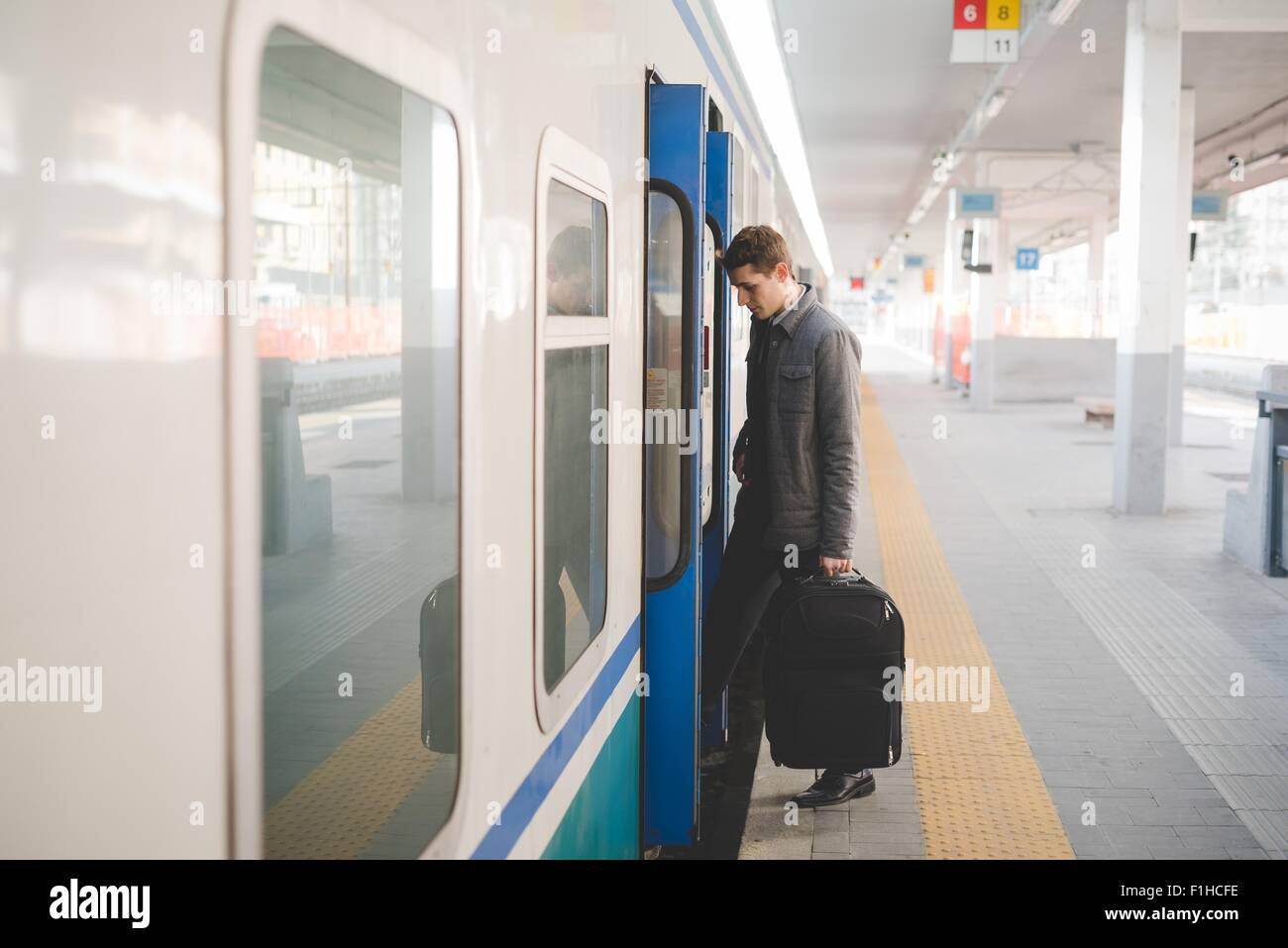 Young businessman commuter boarding train with suitcase. - Stock Image