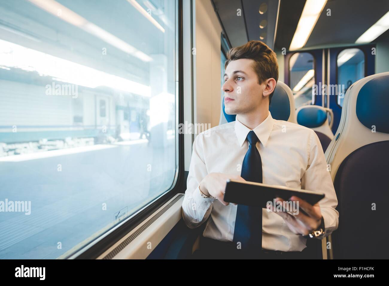 Portrait of young businessman commuter using digital tablet on train. - Stock Image