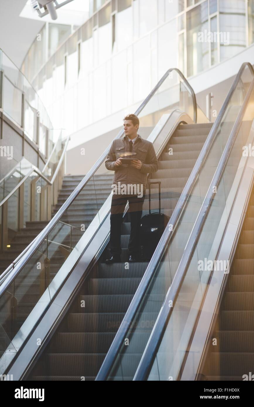 Young businessman commuter on escalator with suitcase. - Stock Image