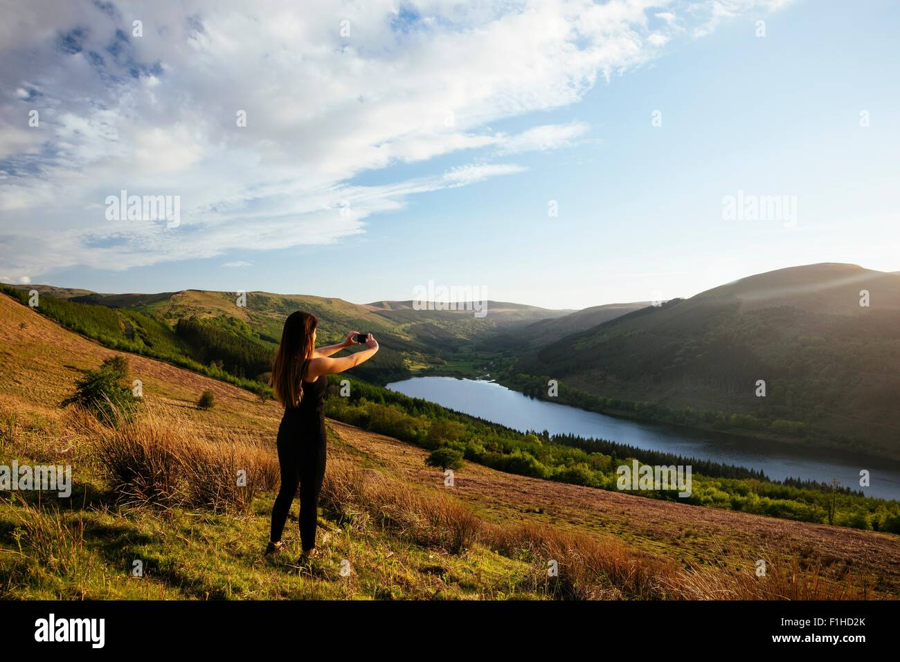 Young woman taking smartphone photograph of Talybont Reservoir in Glyn Collwn valley, Brecon Beacons, Powys, Wales - Stock Image