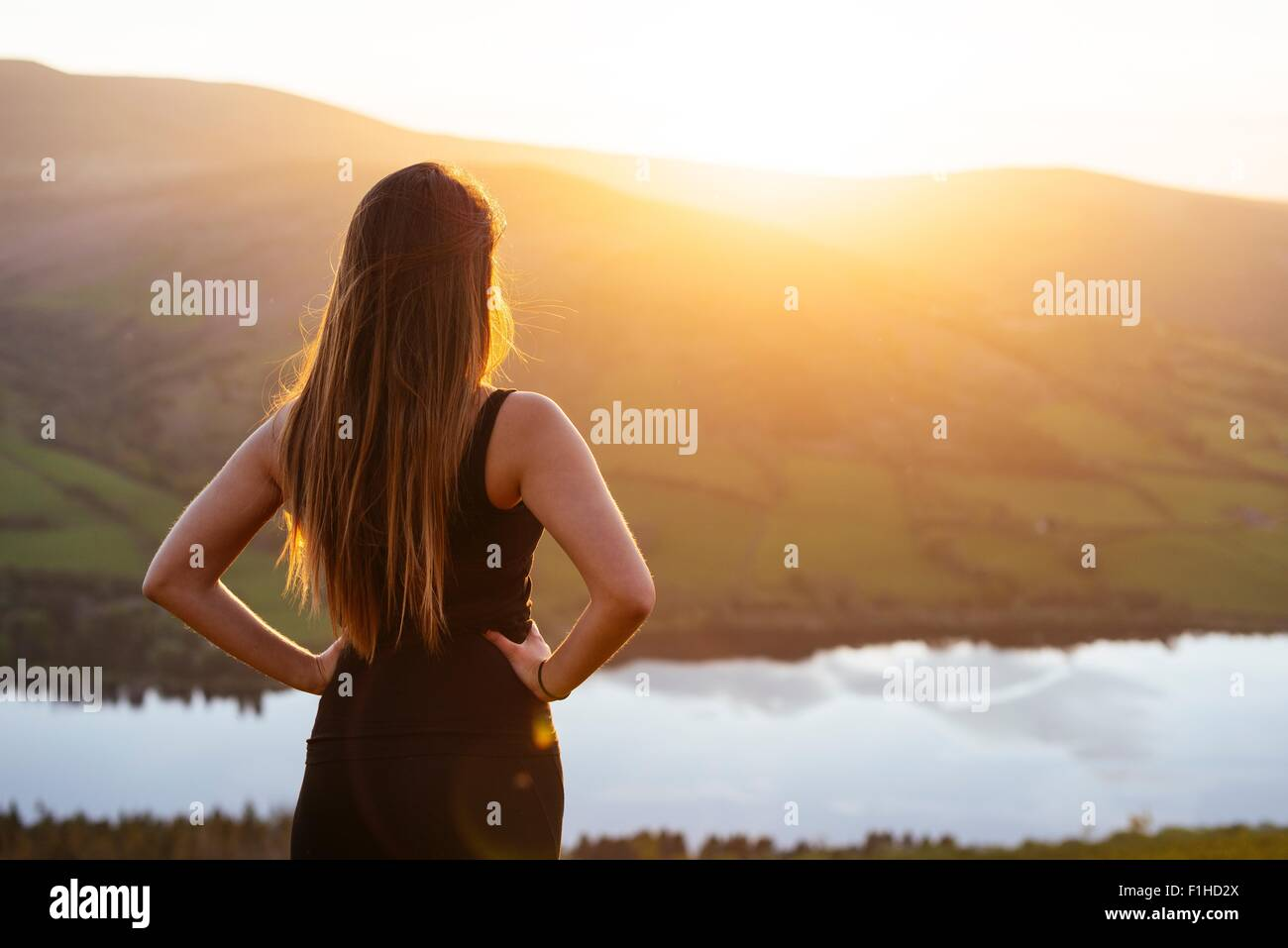 Rear view of young woman looking out over Talybont Reservoir in Glyn Collwn valley, Brecon Beacons, Powys, Wales - Stock Image