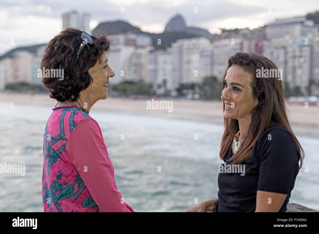 Portrait of mature woman and mother face to face at beach, Copacabana, Rio de Janeiro, Brazil - Stock Image