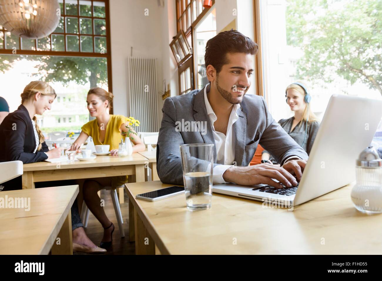 Young man using laptop in cafe - Stock Image