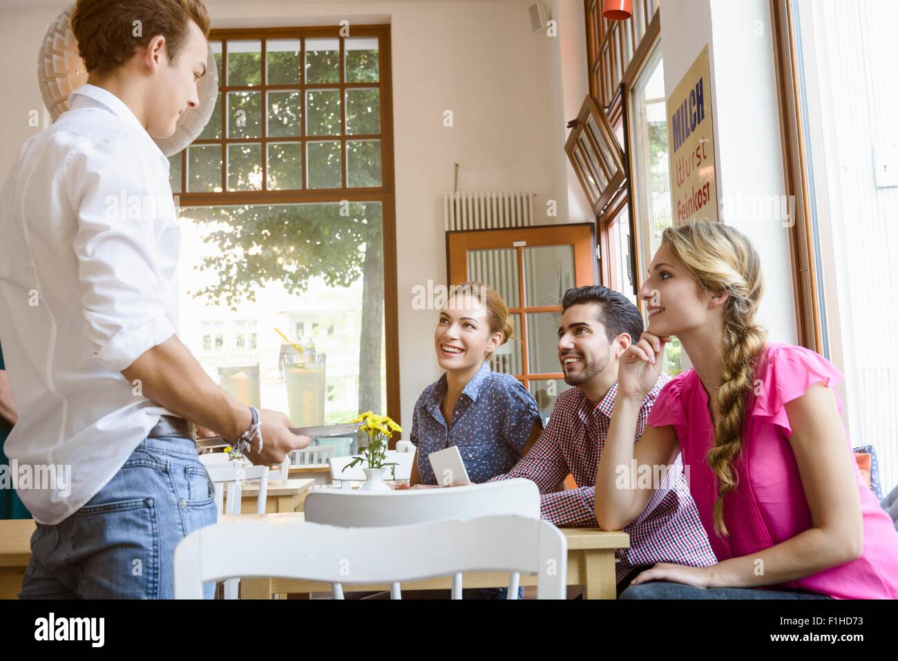 Waiter taking order from young adult friends in cafe - Stock Image