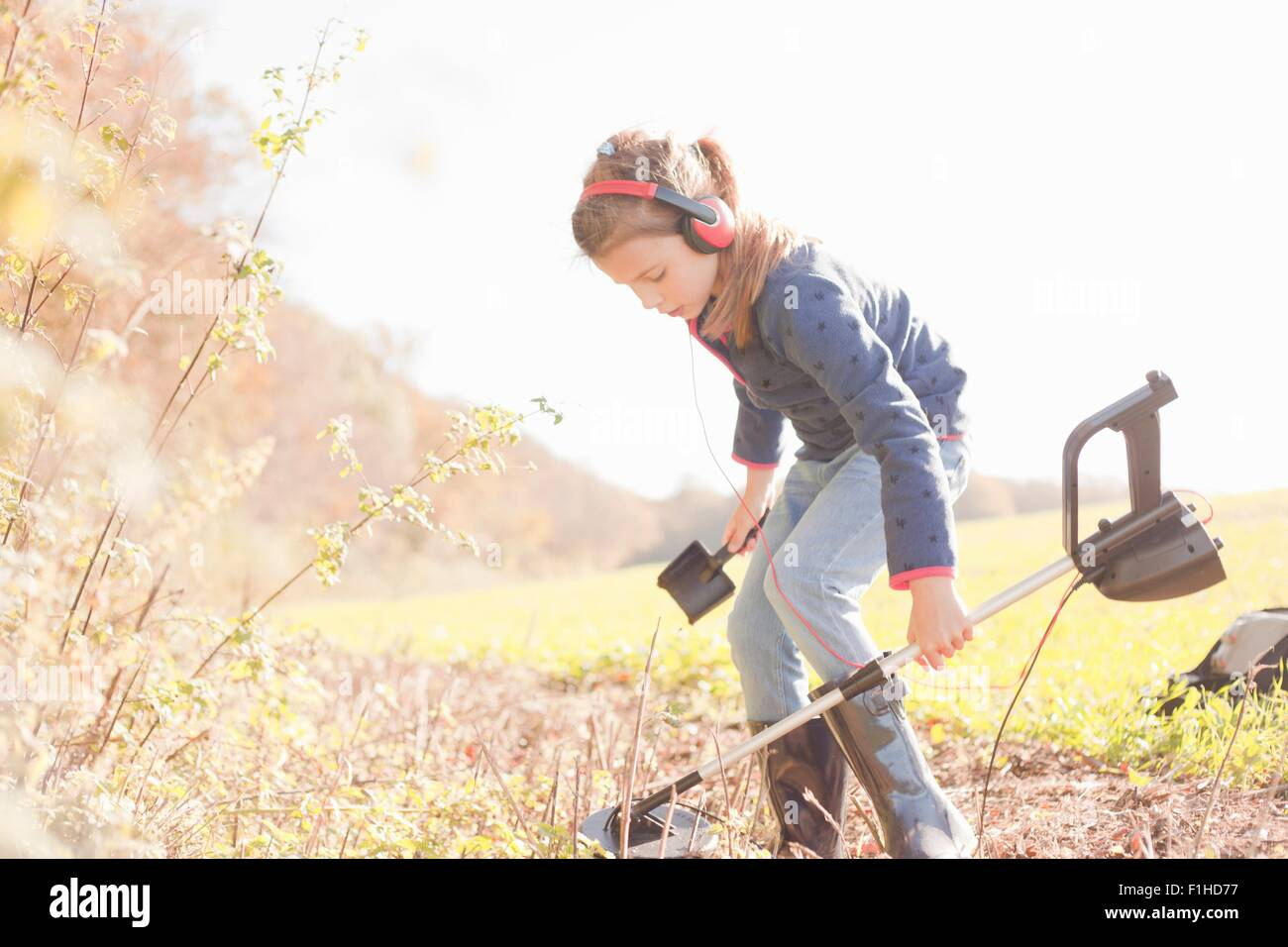 Girl crouching with spade and metal detector in field - Stock Image