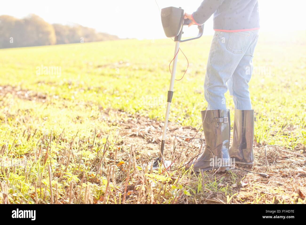 Waist down view of girl using metal detector in field - Stock Image