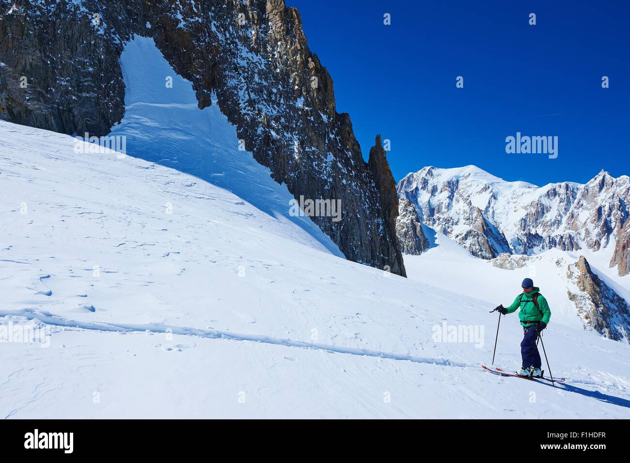 Mature male skier moving up Mont Blanc massif, Graian Alps, France - Stock Image