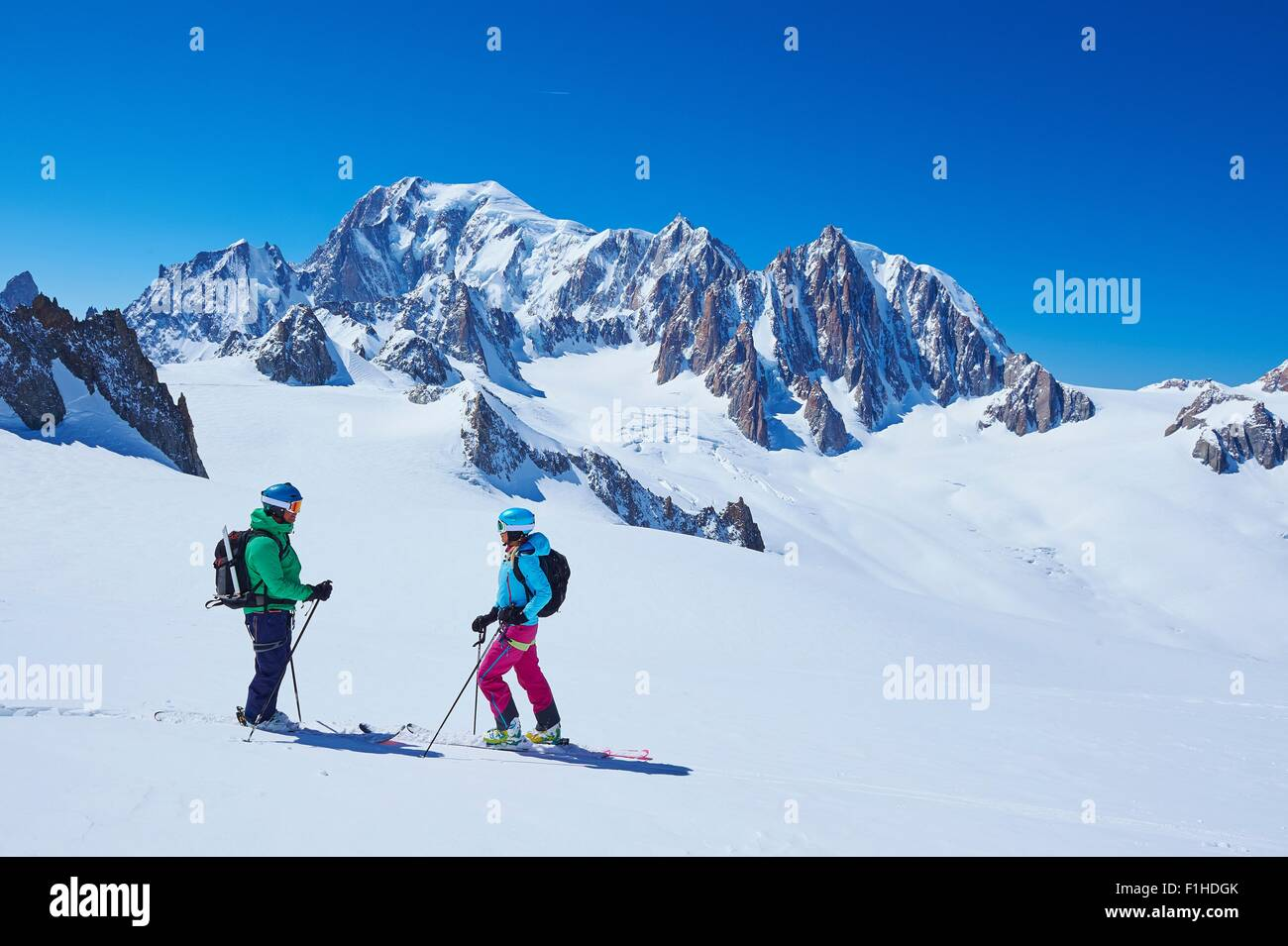 Female and male skiers talking on Mont Blanc massif, Graian Alps, France - Stock Image