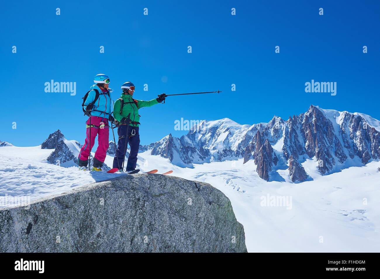 Male and female skiers pointing from ridge on Mont Blanc massif, Graian Alps, France - Stock Image