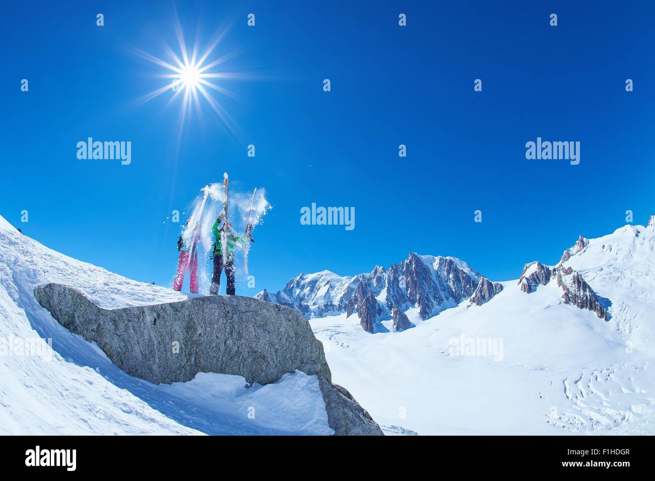 Male and female skiers shaking snow from skis on Mont Blanc massif, Graian Alps, France - Stock Image