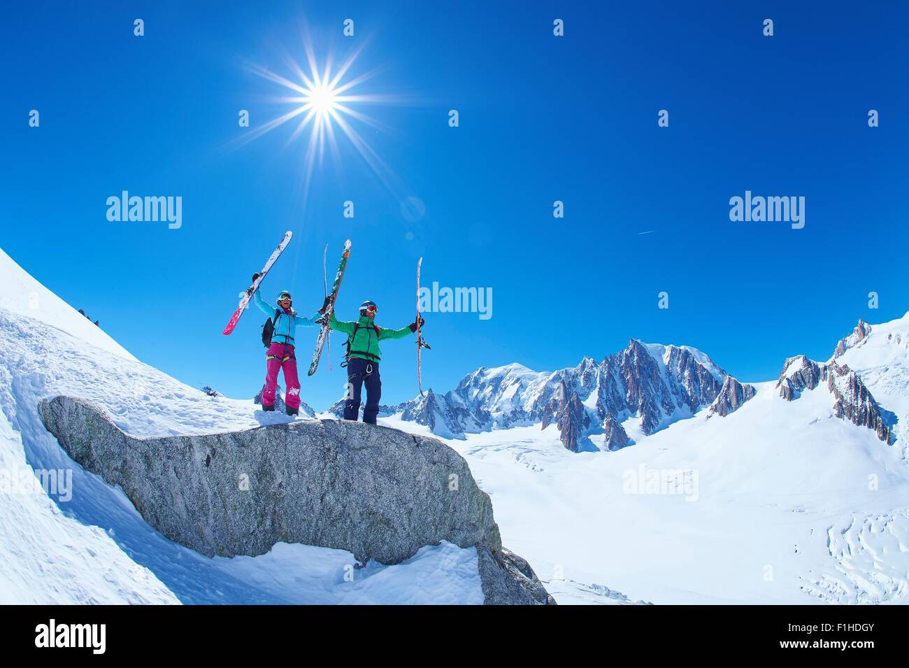 Male and female skiers holding up ski's on Mont Blanc massif, Graian Alps, France Stock Photo