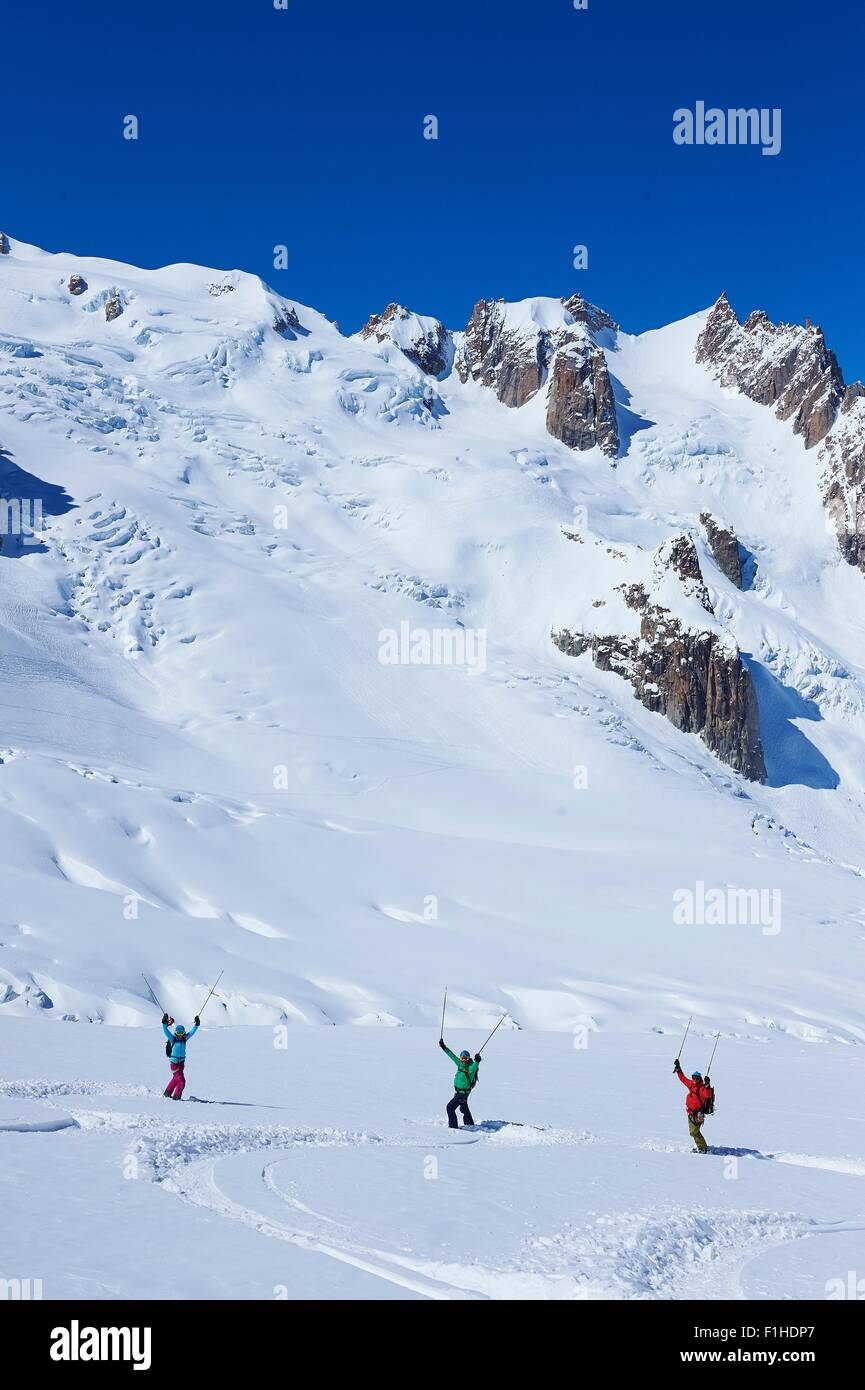 Three adult skiers celebrating on Mont Blanc massif, Graian Alps, France - Stock Image