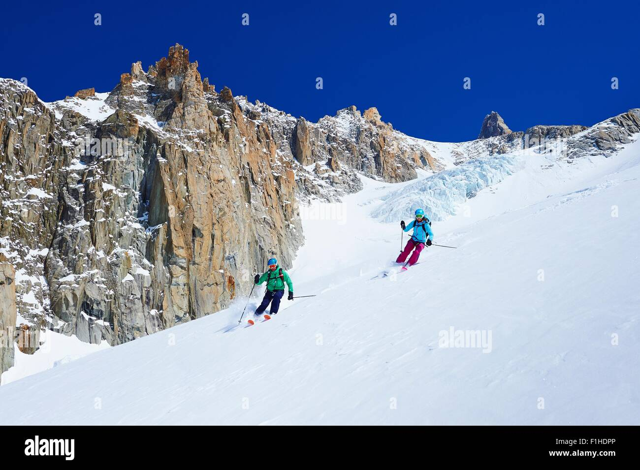 Male and female skiers skiing down Mont Blanc massif, Graian Alps, France - Stock Image