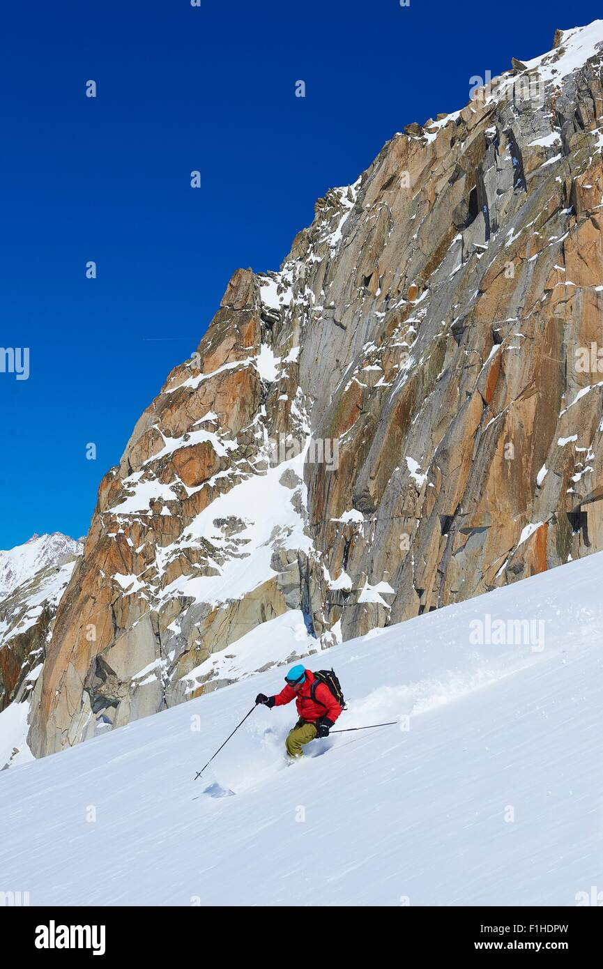 Male skier speeding downhill on Mont Blanc massif, Graian Alps, France - Stock Image
