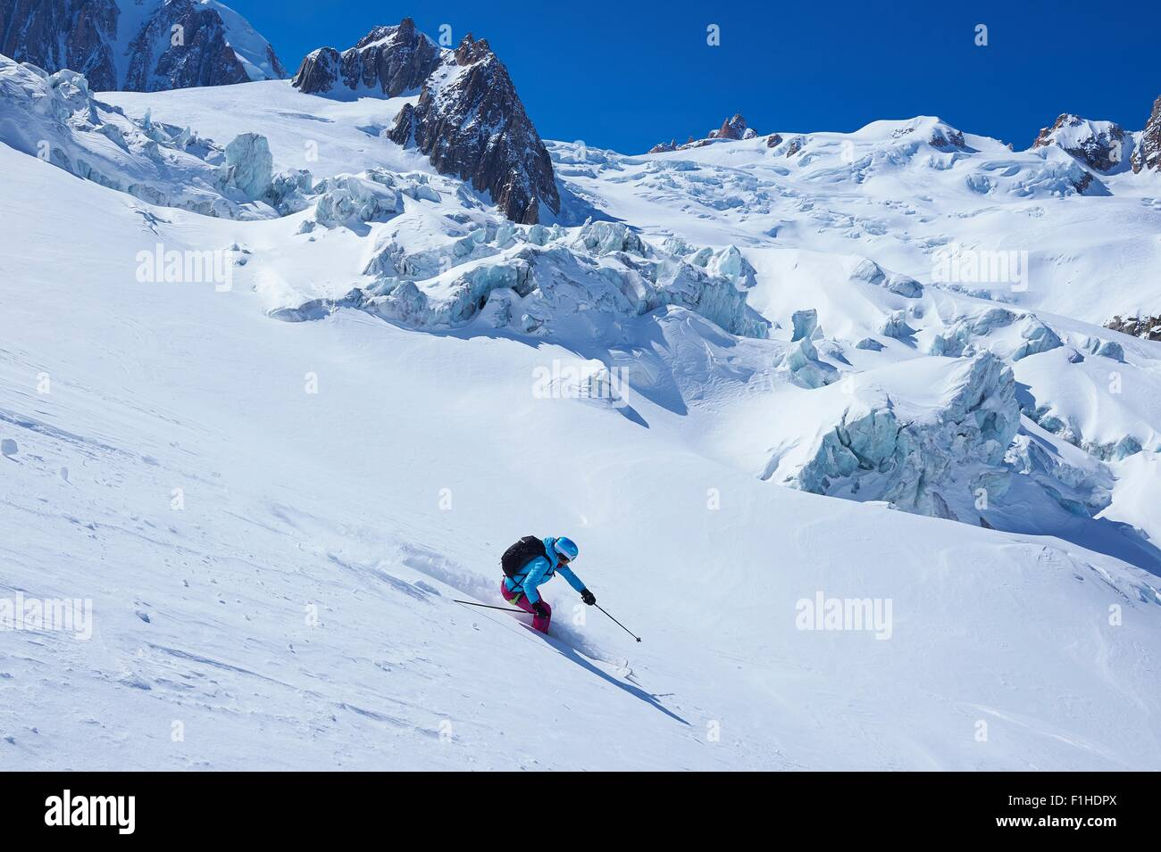 Mature female skier moving downhill on Mont Blanc massif, Graian Alps, France - Stock Image