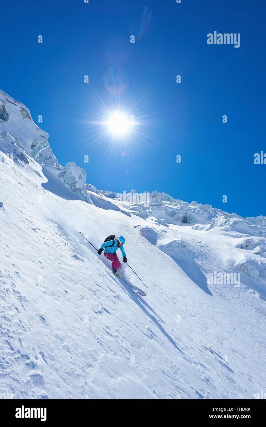 Mature female skier speeding downhill on Mont Blanc massif, Graian Alps, France Stock Photo