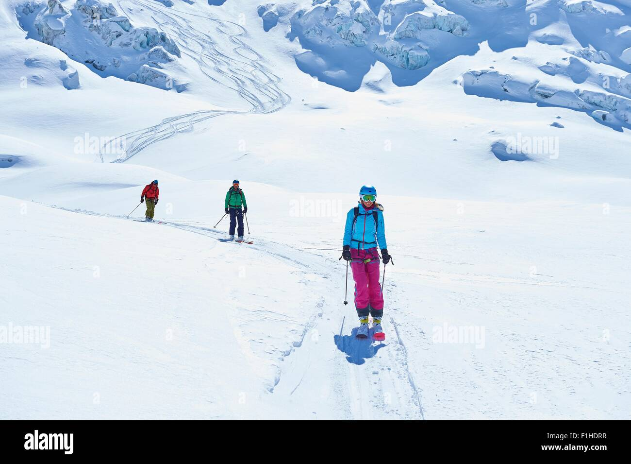 Row of three adult skiers skiing down Mont Blanc massif, Graian Alps, France - Stock Image